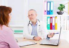 Le docteur parle avec la patiente de femme et s'assied dans le bureau médical Homme dans l'uniforme blanc Assurance-maladie Copie photographie stock