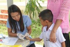 Le docteur prend le sang de l'étudiant primaire images stock