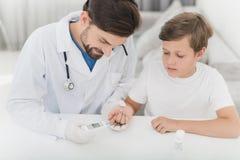 Le docteur prend le sang du garçon avec un doigt utilisant une déchaumeuse Le garçon supporte loyalement la procédure Image stock