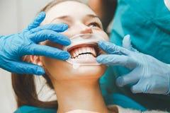 Le docteur regarde l'hygiène buccale professionnelle de dents patientes du ` s Images libres de droits