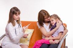 Le docteur regarde la température sur une fille malade de thermomètre et ses conforts de mère Photos stock