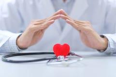 Le docteur remettent le stéthoscope et la forme rouge de coeur dans l'hôpital photographie stock libre de droits