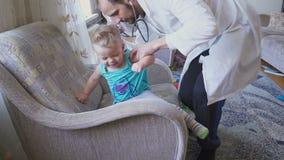 Le docteur rend visite au patient de bébé à la maison Chéri avec le stéthoscope banque de vidéos