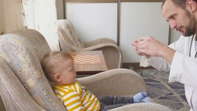 Le docteur rend visite au patient de bébé à la maison Le docteur donne au bébé la médecine d'une cuillère clips vidéos