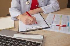 Le docteur s'assied dans un bureau médical dans la clinique et écrit des antécédents médicaux Doctor& x27 de médecine ; table de  Photographie stock