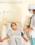 Le docteur soigne le patient avec le stéthoscope. Photo libre de droits