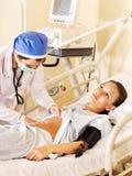 Le docteur soigne le patient féminin avec le stéthoscope. Photos libres de droits