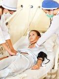 Le docteur soigne le patient féminin avec le stéthoscope. Image stock