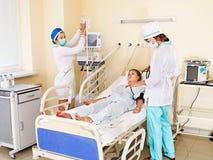 Le docteur soigne le patient féminin avec le stéthoscope. Photographie stock