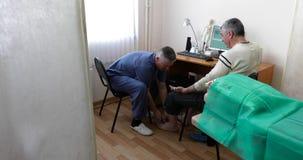 Le docteur soigne le patient dans le bureau banque de vidéos