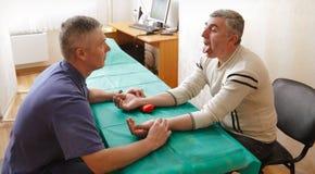Le docteur soigne le patient dans le bureau photographie stock libre de droits