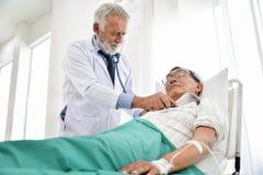 Le docteur supérieur examine un patient asiatique Images stock