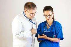 Le docteur supérieur vérifie les résultats du traitement et des entretiens du patient à un autre docteur image stock