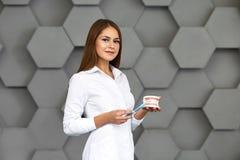 Le docteur sur la brosse à dents serrant la conception de l'avant-projet de pâte dentifrice Fond beige photo stock
