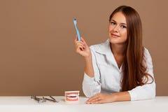 Le docteur sur la brosse à dents serrant la conception de l'avant-projet de pâte dentifrice Fond beige photo libre de droits