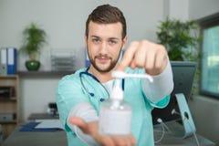 Le docteur tenant l'antibactérien de distributeur de pompe lavent à la main Photo stock