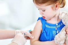 Le docteur tient un enfant de vaccination d'injection photo stock