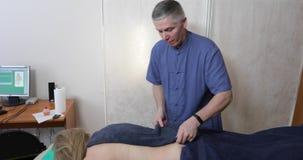 Le docteur traite le dos du ` s de femme banque de vidéos
