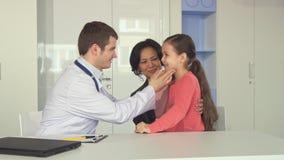 Le docteur vérifie vers le haut de la petite fille au bureau image stock