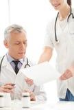 Le document au signe. Jeune docteur féminin gai tenant un Doc. Images stock
