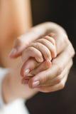 Le doigt de chéri de la mère nouveau-née de fixation Image libre de droits