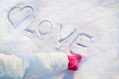 Le doigt de fille dans les gants rouges dessine un coeur dans la neige et l'amour de mot Fin vers le haut Photos libres de droits