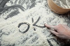"""Le doigt femelle écrit le mot """"correct """"sur la farine blanche Le concept de la cuisson faite maison image libre de droits"""