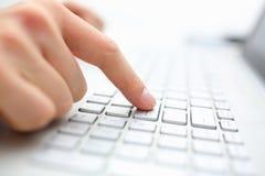 Le doigt masculin de main appuie sur la touche de pénétrer dans sur le clavier d'ordinateur portable Images stock
