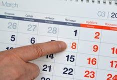 Le doigt masculin indique le nombre le 8 mars dans le calendrier photo libre de droits
