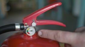 Le doigt montre quelle pression devrait être dans l'extincteur, c photographie stock
