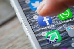 Le doigt supprime Facebook APP sur l'écran d'iPhone photographie stock libre de droits