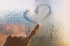 Le doigt sur le verre humide dessine le coeur photos stock