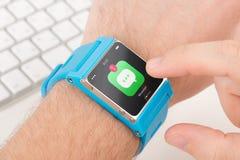 Le doigt tape l'icône de messager sur la montre intelligente bleue Image libre de droits