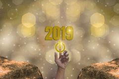 Le doigt touchent le bouton marche à commencer le thème 2019 d'éclat de l'or, bonne année avec le bokeh léger d'or de scintilleme illustration libre de droits