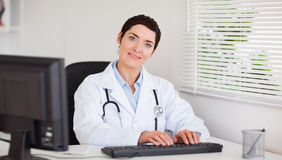 Le doktor som skrivar med henne datoren Arkivfoton