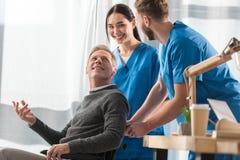 le doktorer och patienten på rullstolsamtal royaltyfri bild