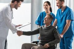 le doktorn och patienten på rullstolen royaltyfri foto