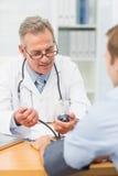 Le doktorn som tar hans patienter blodtryck Arkivbild