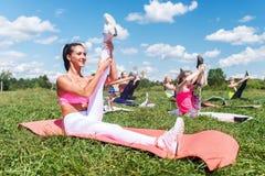 Le donne adatte che fanno gli esercizi che allungano i tendini del ginocchio che di sollevamento la forma fisica delle gambe clas Fotografie Stock Libere da Diritti