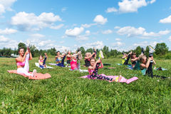 Le donne adatte che fanno gli esercizi che allungano i tendini del ginocchio che di sollevamento la forma fisica delle gambe clas Fotografia Stock
