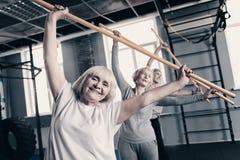Le donne allegre che fanno l'allungamento con l'esercizio di legno attacca Immagini Stock Libere da Diritti
