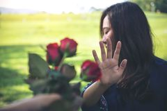 Le donne asiatiche che rifiutano una rosa rossa fioriscono dal suo ragazzo il giorno del ` s del biglietto di S. Valentino fotografia stock libera da diritti
