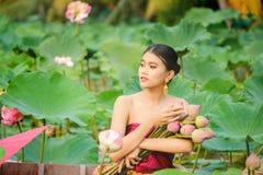 Le donne asiatiche che si siedono sulle barche di legno raccolgono il loto fotografia stock