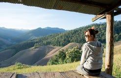 Le donne asiatiche che si siedono in un cottage con i giacimenti ed il cereale verdi delle montagne del paesaggio coltivano di ma Fotografie Stock