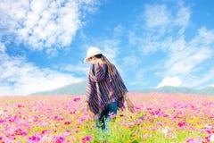 Le donne asiatiche del viaggiatore che camminano nel giacimento e nella mano di fiore toccano il fiore dell'universo, Immagine Stock