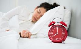 Le donne asiatiche dormono sul letto con la sveglia di mattina sopra Fotografie Stock