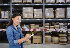 Le donne asiatiche scrivono la nota degli ordini al magazzino della fabbrica immagini stock