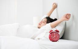 Le donne asiatiche svegliano da sonno è l'allungamento lei stessa nel MOR Fotografia Stock Libera da Diritti