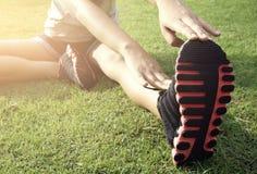 Le donne attraenti si scaldano l'allungamento dell'esercizio le loro gambe prima di w Fotografia Stock