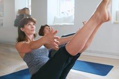 Le donne in barca piena posano durante la sessione di yoga Fotografia Stock Libera da Diritti